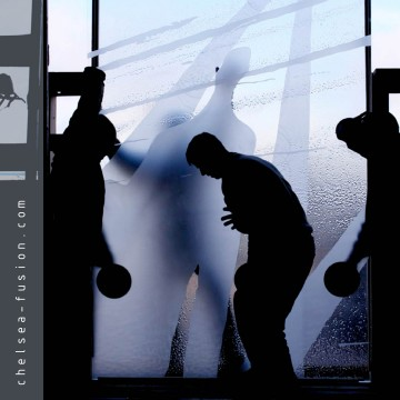 silhouetted glaziers handling kiln formed translucent glass with sandblasted frosted pattern